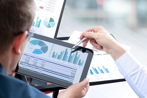 Menschen betrachten Grafiken auf Tablet. Bildlich für Analyse Gesamtsituation vor Gründung einer Stiftung in Liechtenstein.