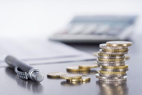 Münzen, Stift und Taschenrechner - bildlich für Stiftungsvermögen im Zusammenhang mit Stiftung Liechtenstein